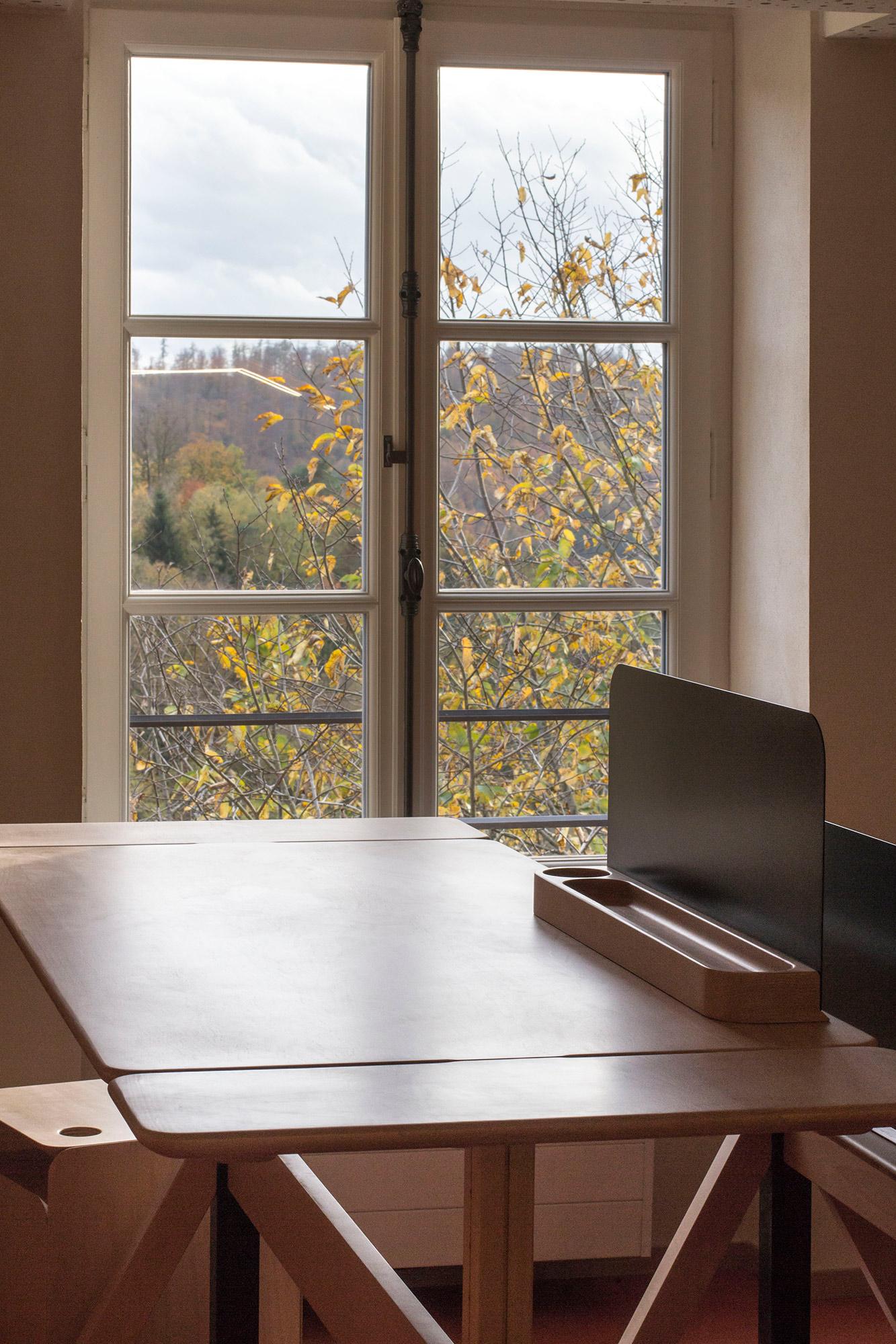 Bureau et micro-cloison de la gamme de mobilier Wood Wide Web, devant une fenêtre avec vue sur la forêt des Vosges du Nord