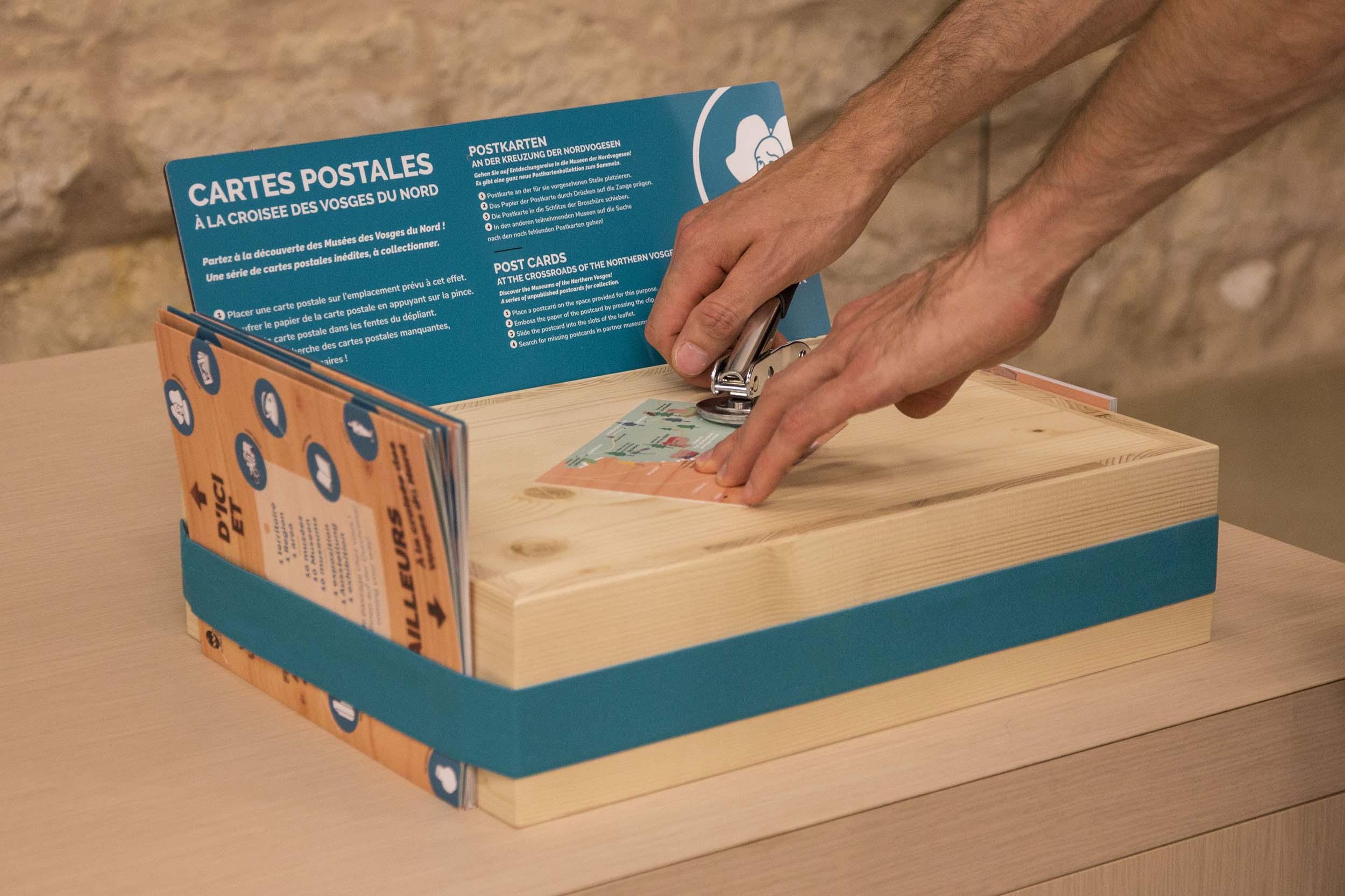 Manip muséographique avec un jeu de cartes postales à gaufrer pour les collectionner. En lien avec l'exposition itinérante D'ici et d'ailleurs, à la croisée des Vosges du nord
