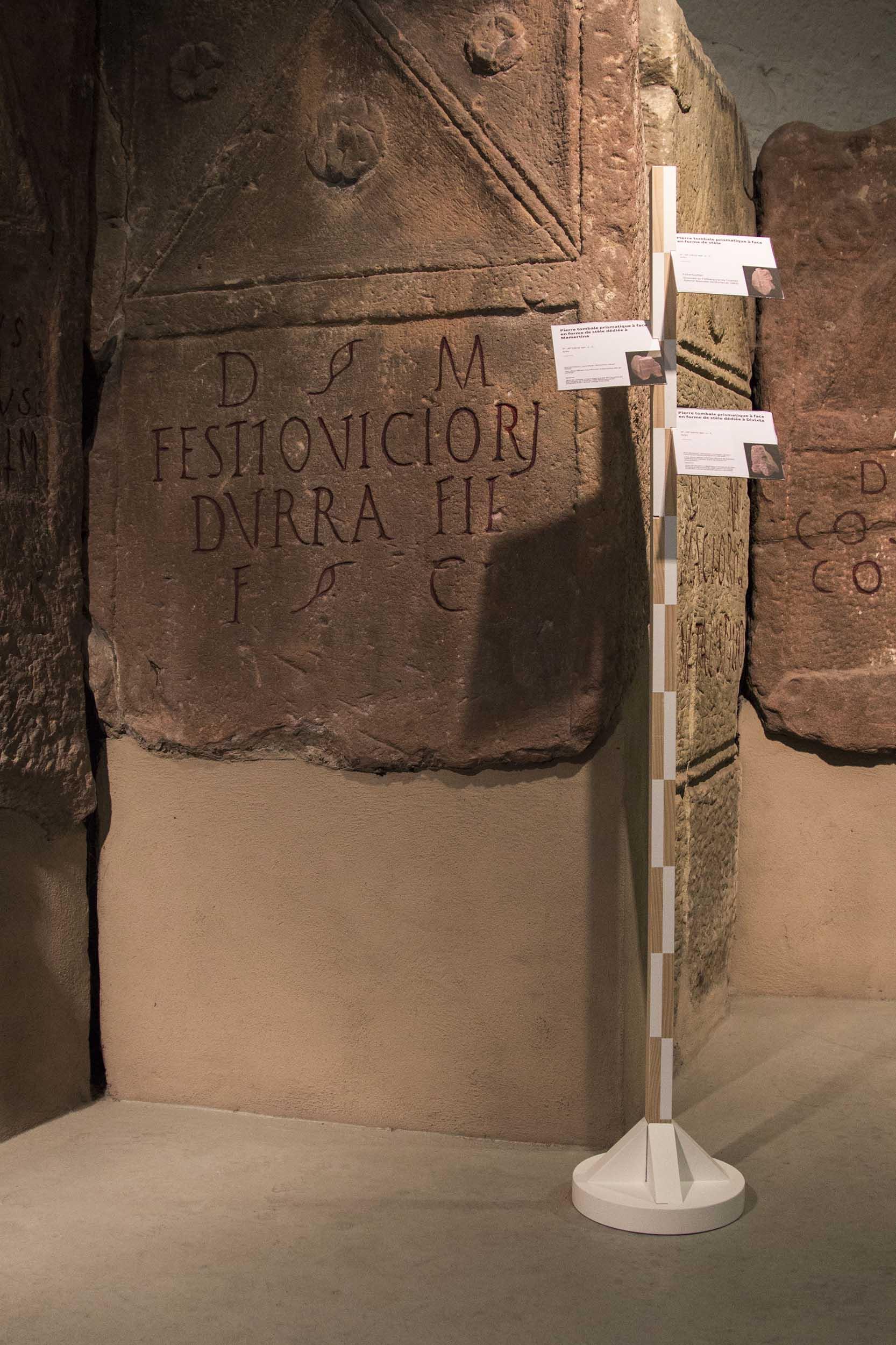 Porte-cartels sur pied en bois installé parmi les stèles de la section archéologique du Musée du Château des Rohan de Saverne